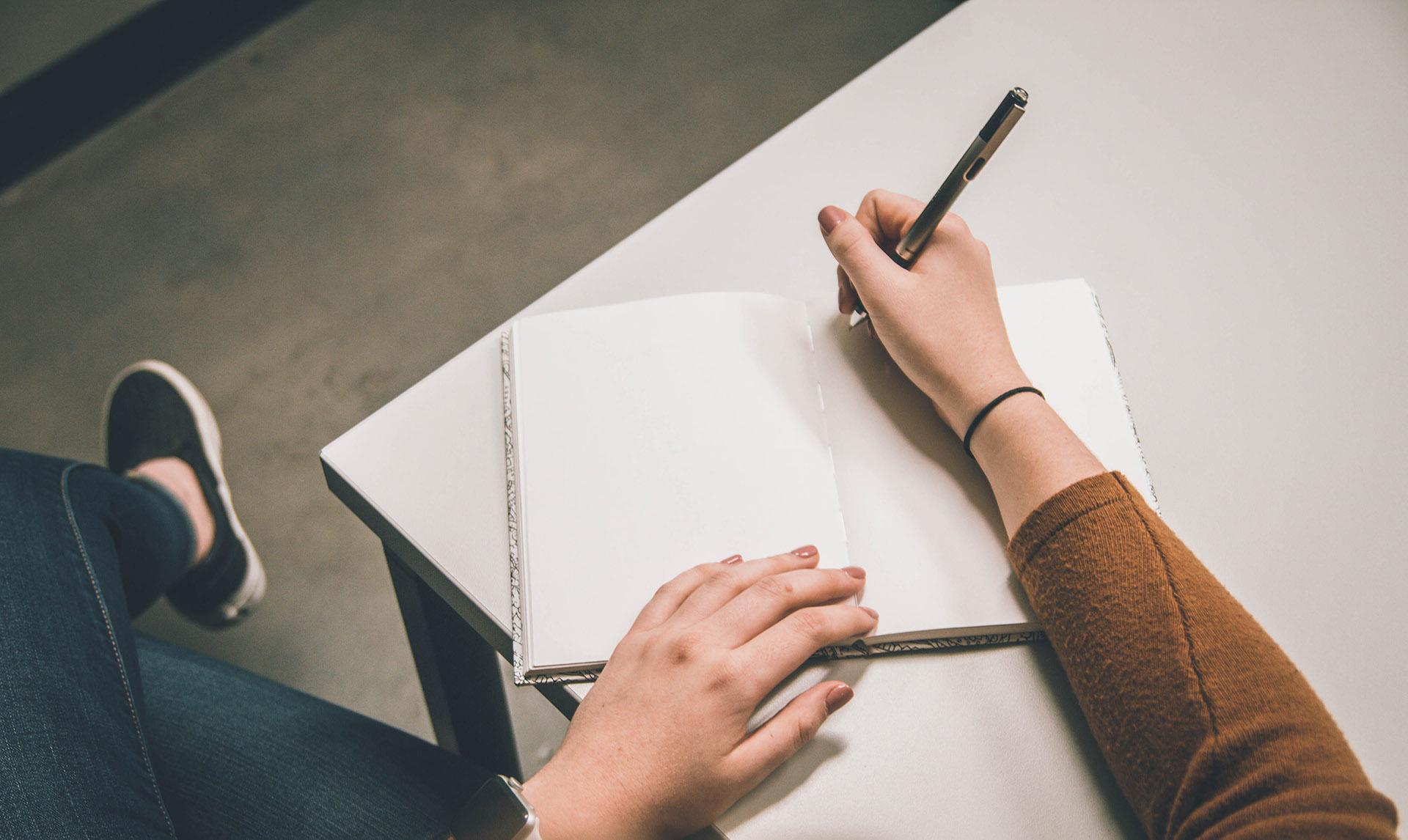 Kädet kynä ja kirjoituspaperia