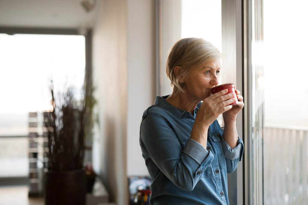 Nainen katsoo ikkunasta ulos simaisten punaisesta kahvikupista