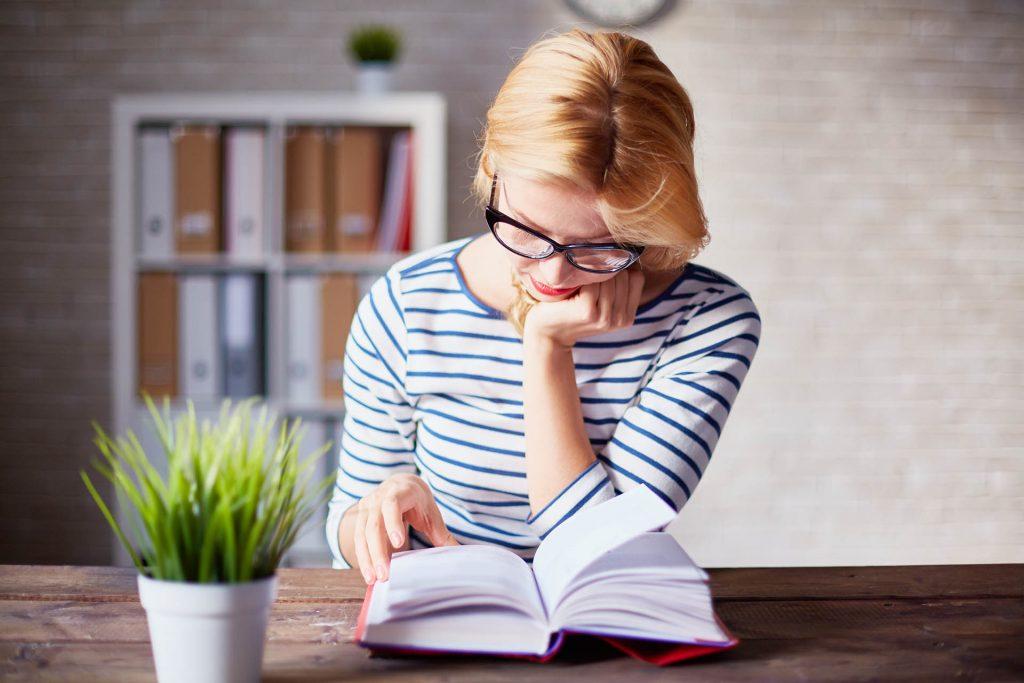 Nuori nainen lukee pöydän ääressä keskittyneenä