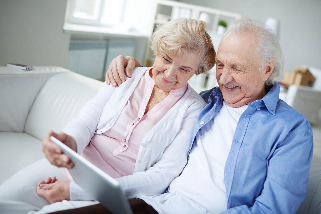 Vanhempi pariskunta nauraa läppärin ääressä sohvalla