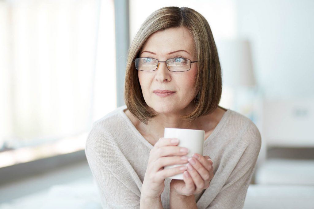 Varttunut nainen katsoo kameraan kahvikuppi kädessään