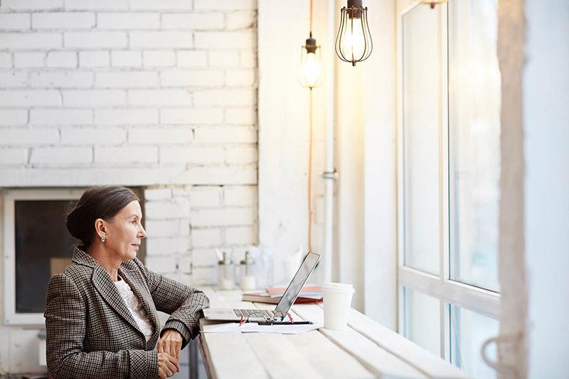 Artikkelikuva-varttunut-nainen-istuu-toimistopöydän-ääressä-hymyillen
