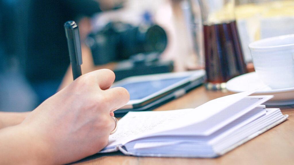 Kasi valmiina kirjoittamaan muistikirjaan kynan kera