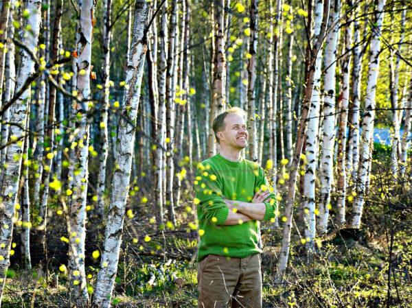 Kirjailija Petri Tamminen seisoo aurinkoisessa koivikossa