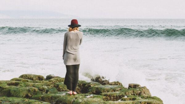 Nainen katselee merta sammaleisilla kallioilla
