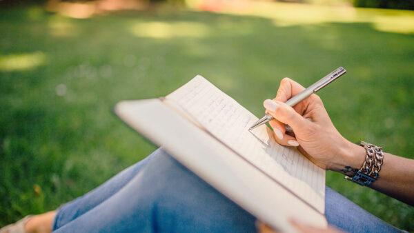 Nainen kirjaa muistikirjaan asioita nurmikolla