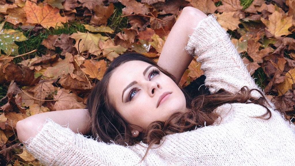 Nuori nainen katsoo taivasta maaten syksyisilla lehdilla ajatuksissaan