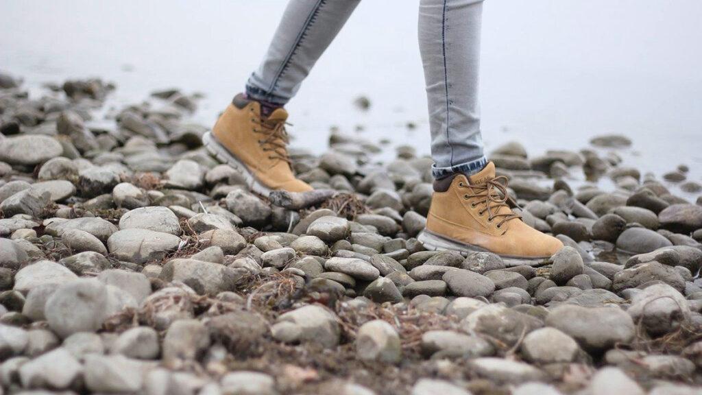 Vaelluskengissa kulkeva nainen rantakivien paalla kavellen