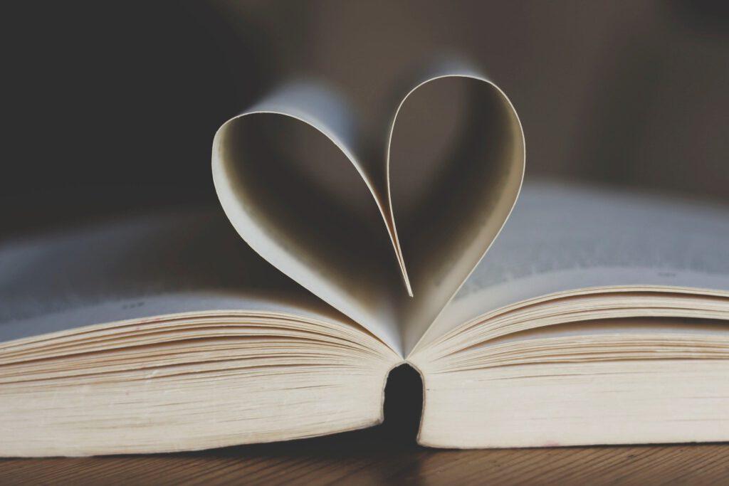 Kirja avonaisena kaksi sivua sydamen muotoon avattuna