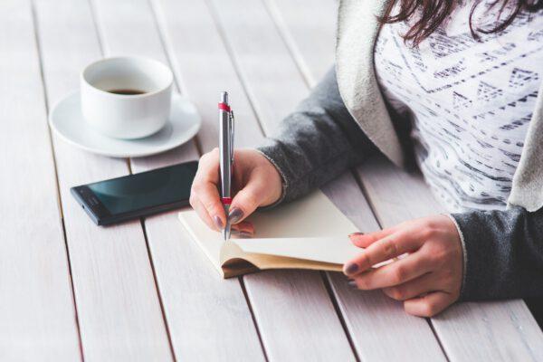 Nainen kirjoittaa muistikirjaan